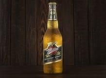 MINSK VITRYSSLAND - JUNI 29, 2017: Redaktörs- foto av Miller Genuine Draft Beer på mörk träbakgrund Mjölnaren är fotografering för bildbyråer