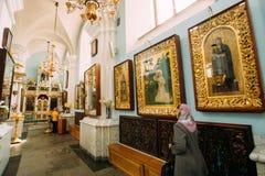 Minsk, Vitryssland Kvinnaförsamlingsbo som ber i domkyrka av helgedom S Arkivfoton