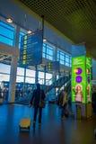MINSK VITRYSSLAND - MAJ 01 2018: Inomhus sikt av oidentifierade turister som går med deras luggages under ett informativt tecken Arkivbild