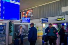 MINSK VITRYSSLAND - MAJ 01 2018: Oidentifierat folk som går med deras luggages och håller ögonen på en avvikelseskärm som lokalis Arkivbilder