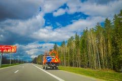 MINSK VITRYSSLAND - MAJ 01, 2018: Ooutdoor sikt av tungt maskineri i huvudvägen till flygplatsen av Minsk mot dramatiskt Arkivfoto