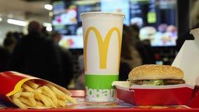 Minsk Vitryssland, Maj 18, 2017: Stor Mac-hamburgaremeny i en restaurang för McDonald ` s på en oskarp bakgrund av kunder som bes lager videofilmer