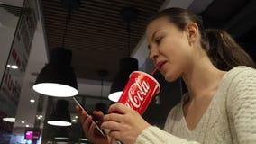 MINSK Vitryssland-oktober 30, 2017: Coca - colaläsk Kvinnan dricker en coca - cola och använder en smartphone på ett kafé stock video