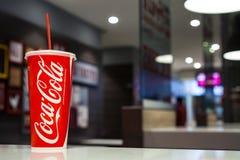 MINSK Vitryssland-oktober 30, 2017: En pappers- kopp av cocaen - cola på en kafétabell Arkivfoton