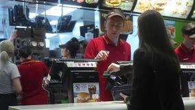 Minsk, Weißrussland, am 14. April 2018: Besucher bestellt Lebensmittel und zahlt Kreditkarte an McDonald-` s Restaurant stock footage