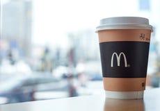 Minsk, Weißrussland, am 18. Februar 2018: Papiertasse kaffee mit McDonald-` s Logo auf Tabelle nahe Fenster auf Hintergrund der u Lizenzfreie Stockbilder