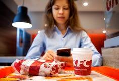 Minsk, Weißrussland, am 21. Juli 2018: Sandwich und Papierschale auf Tabelle in KFC-Restaurant Frau wird das Mittagessen essen un Stockfoto