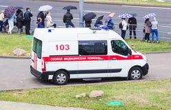 MINSK, WEISSRUSSLAND - 3. JULI 2018: Ein modernes Krankenwagenauto ist in der Stadt, dort sind Leute mit Regenschirmen, Regen lizenzfreies stockfoto