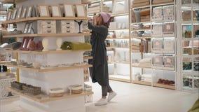 MINSK, WEISSRUSSLAND - 10. OKTOBER 2017 Innerhalb Einzelhandelsgeschäftes Zara Homes in Minsk Eine junge Hippie-Frau wählt Haupt- Lizenzfreies Stockfoto