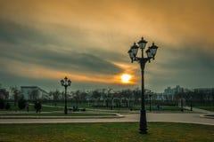 MINSK, WIT-RUSLAND - April 15, 2018: stegen met straatlantaarns in een avondpark tegen een bewolkte hemel en een zonsondergang stock foto