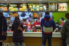 Minsk, Wit-Rusland, 8 Januari, 2018: De mensen geven opdracht tot voedsel in een Restaurant van McDonald ` s Stock Foto