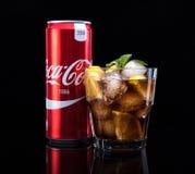 MINSK, WIT-RUSLAND - JANUARI 05, 2017: De redactiefoto kan en glas van Coca-Cola met ijs op donkere achtergrond Coca-Cola is Stock Foto
