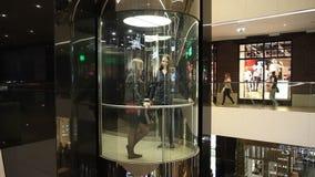 Minsk, Wit-Rusland, 9 juli, 2017: De meisjes berijden in een glasliften op de achtergrond van winkels in de wandelgalerij` Galeri stock videobeelden