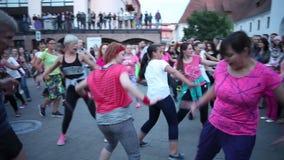 Minsk, Wit-Rusland - 15 juli 2017: De menigte herhaalt bewegingen in openlucht van de dansleraar, actieve dansen van mensen van v stock video
