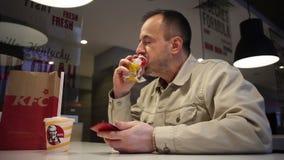 Minsk, Wit-Rusland, 5 juli, 2017: De mens eet lunch met grote eetlust in een restaurant KFC en het gebruiken van smartphone Het m stock footage