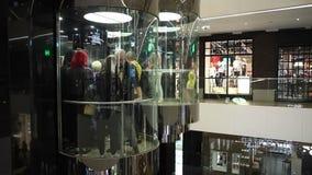 Minsk, Wit-Rusland, 9 juli, 2017: De mensen berijden in een glasliften op de achtergrond van winkels in de wandelgalerij` Galerij stock videobeelden