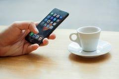 Minsk, Wit-Rusland, 17 juli, 2017: Hand die Iphone met mobiele toepassingspictogrammen gebruiken met een kop van koffie op de lij Royalty-vrije Stock Afbeeldingen