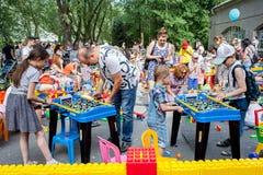 Minsk, Wit-Rusland, 3 Juni, 2018: De kinderen met ouders spelen lijstvoetbal en andere spelen op speelplaats met heel wat speelgo Royalty-vrije Stock Afbeelding