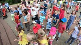 Minsk, Wit-Rusland, 3 Juni, 2018: De kleine dankbare toeschouwers die vermaakprogramma staren hebben pret en dans in openlucht in stock video