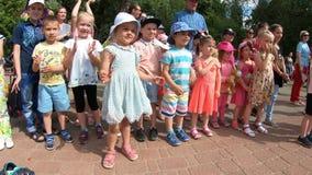 Minsk, Wit-Rusland, 3 Juni, 2018: Kleine dankbare toeschouwers die overleg staren en in park in openlucht toejuichen stock videobeelden