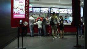 Minsk, Wit-Rusland, 3 Mei, 2018: De mensen geven opdracht tot voedsel in een KFC-Restaurant stock videobeelden