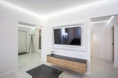 MINSK, WIT-RUSLAND - NOVEMBER 21, 2016: de binnenlandse zolder van de luxurezaal vlak in grijs stijlontwerp met TV stock fotografie