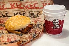 MINSK, WIT-RUSLAND - november 28, 2017: Hamburger en document kop met KFC-embleem op lijst in KFC-Restaurant stock fotografie
