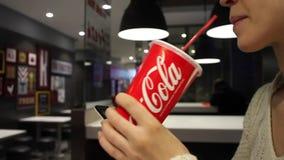 MINSK, 30 Witrussisch-Oktober, 2017: De frisdrank van Coca-Cola De vrouw drinkt Coca-Cola en gebruikt een smartphone op een koffi stock video