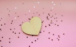 Minsta begrepp av trähjärta mot pastellfärgad rosa bakgrund med brusandestjärnakonfettier arkivbild