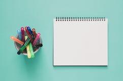 Minsta begrepp för kontorsarbetsplats Tom anteckningsbok- och färgpenna b Royaltyfri Foto