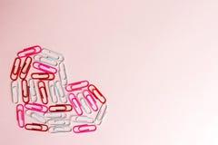 Minsta begrepp Hjärtasymbol som göras av brevpappergem på rosa bakgrund Lekmanna- lägenhet, bästa sikt Arkivfoto