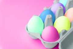 Minsta begreppspåsk Ägg i neonfärger Minsta bakgrund royaltyfri bild