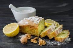 Mint cake on black surface with lemon, nuts, powdered sugar.  Stock Photo