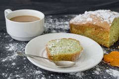 Mint cake sprinkled with powdered sugar on dark surface with coffee cup stock image
