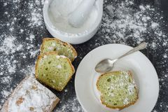 Mint cake sprinkled with powdered sugar on dark surface with coffee cup.  Stock Photography