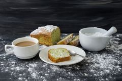 Mint cake sprinkled with powdered sugar on dark surface with cup of coffee.  Stock Photos