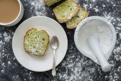 Mint cake sprinkled with powdered sugar on dark surface with cup of coffee.  Royalty Free Stock Photo