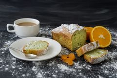 Mint cake sprinkled with powdered sugar on dark surface with fresh oranges mandarins royalty free stock image