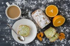 Mint cake sprinkled with powdered sugar on dark surface with fresh oranges mandarins. Mint cake sprinkled with powdered sugar on dark surface with fresh oranges Royalty Free Stock Photos