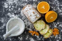 Mint cake sprinkled with powdered sugar on dark surface with fresh oranges mandarins. Mint cake sprinkled with powdered sugar on dark surface with fresh oranges Royalty Free Stock Image