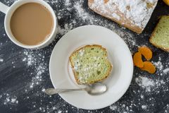 Mint cake sprinkled with powdered sugar on dark surface with fresh oranges mandarins stock image