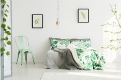 Mint chair in inspiring bedroom. Mint chair next to king-size bed with floral bedsheets in inspiring bedroom with leaves paintings stock images