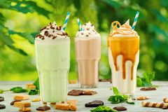 Mint, chocolate and caramel milkshakes. Mint, chocolate and salted caramel milkshakes with beautiful on a terrace table. Stay cool in hot summer with tasty dairy stock image
