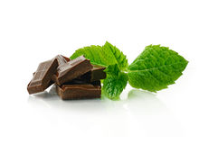 Mint Chocolate 2. Studio macro of dark chocolate pieces with fresh green mint leaves on a white surface. Copy space royalty free stock photo