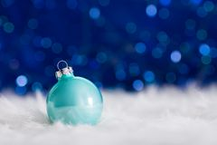 Mint Christmas ball on white fur with garland lights on blue bok Royalty Free Stock Photography