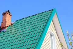 Mint color tiled roof and brick chimney. Stock Photography