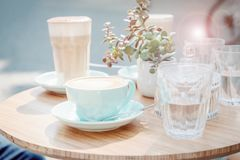 Mint cup of coffee cappuccino and glass with coffee latte in a street cafe. Sun glare effect. Pastel toned photo. Mint color cup of coffee cappuccino and glass stock photography