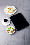 Mint eclairs on a plate, coffee and digital tablet with white sc Stock Photo