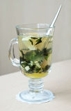 Mint and ginger tea. Transparent glass full of healthy hot herbal tea made of cut ginger root, green mint leaves and honey, spoon in the glass, on a table in the Royalty Free Stock Photos
