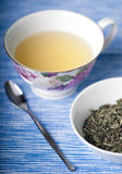 Mint Green Herbal Tea. Cup of mint green herbal tea in teacup next to dish of dried tealeaves royalty free stock photos